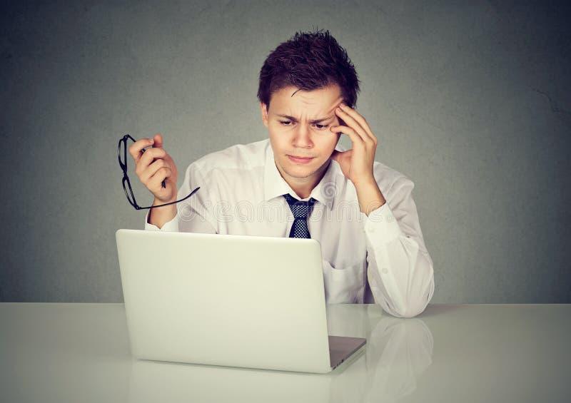 有玻璃工作的绝望雇员人在膝上型计算机 免版税图库摄影