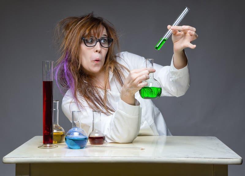 有玻璃烧瓶的做鬼脸的工作的科学家 库存照片