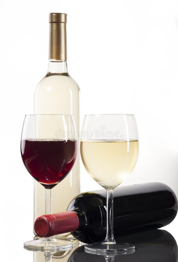 有玻璃的红色和白葡萄酒瓶 库存照片