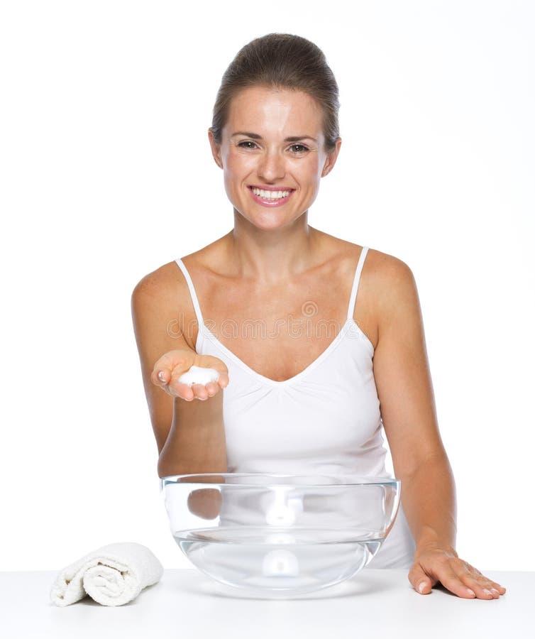 有玻璃碗的愉快的少妇用水洗涤的手 图库摄影
