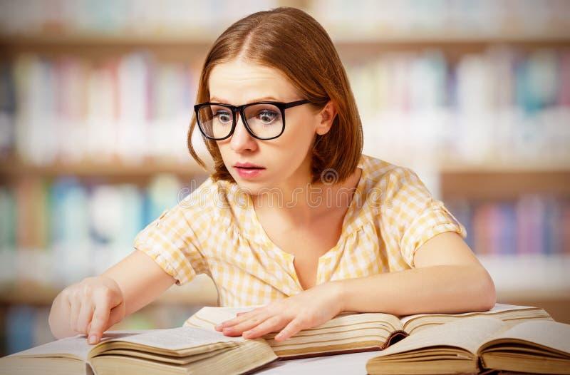 有玻璃阅读书的滑稽的惊奇的女孩 免版税库存图片