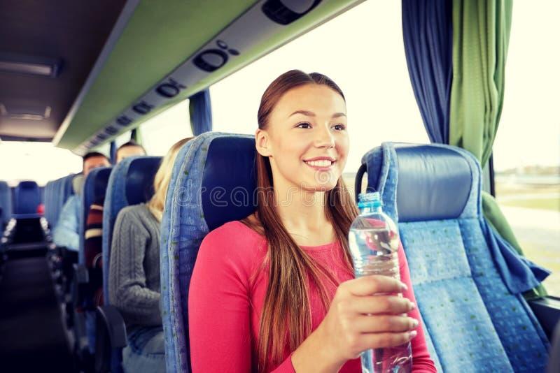 有水瓶的愉快的少妇在旅行公共汽车上 库存照片