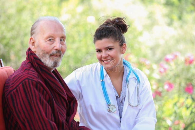 有医生或护士的微笑的资深患者 免版税库存图片