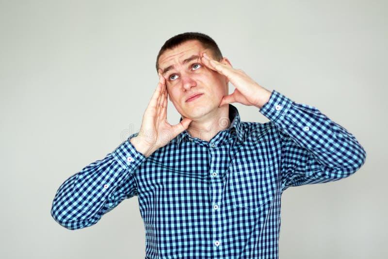 有头疼人年轻人 在灰色 免版税库存图片