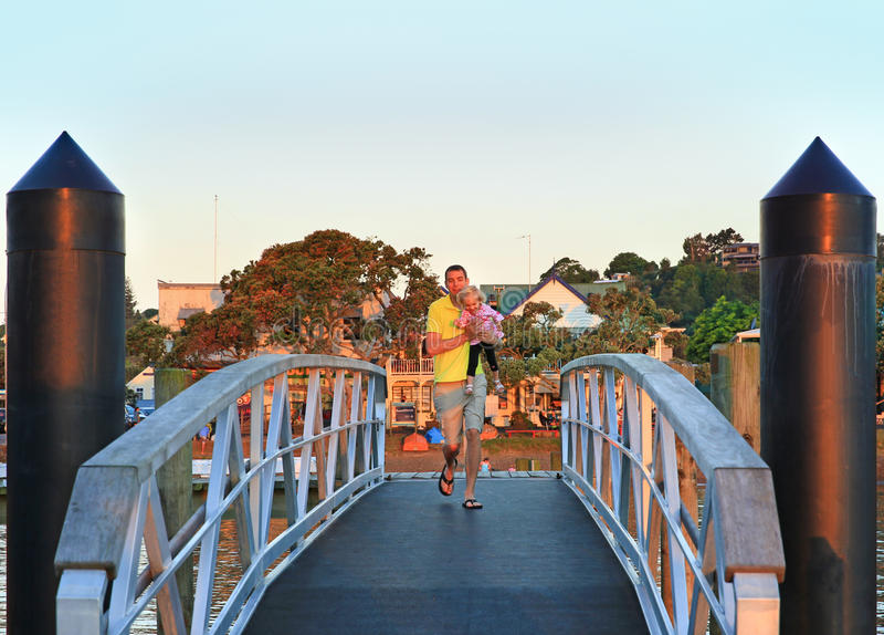 有他的一点女儿赛跑的愉快的年轻父亲 免版税图库摄影
