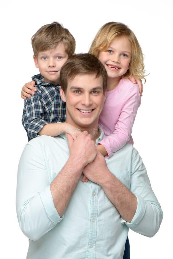 有他的两个孩子的愉快的微笑的年轻父亲 免版税库存照片