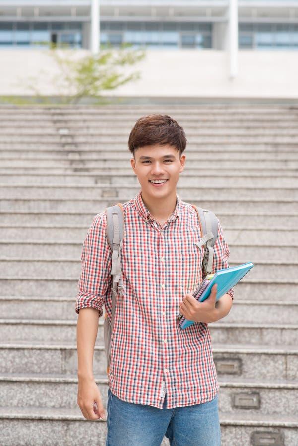有他的书的微笑的学生在大学 免版税库存图片