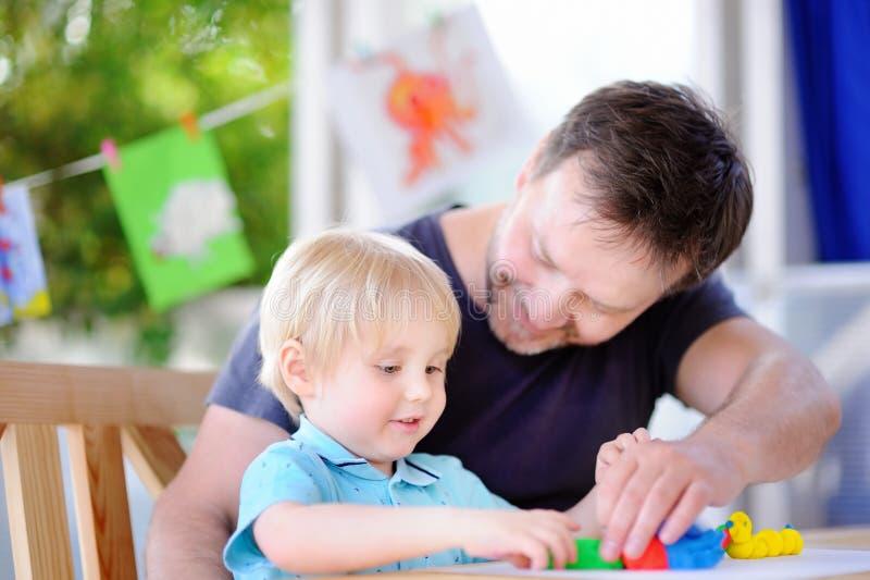 有他的使用与五颜六色的雕塑黏土的父亲的小男孩 免版税库存照片
