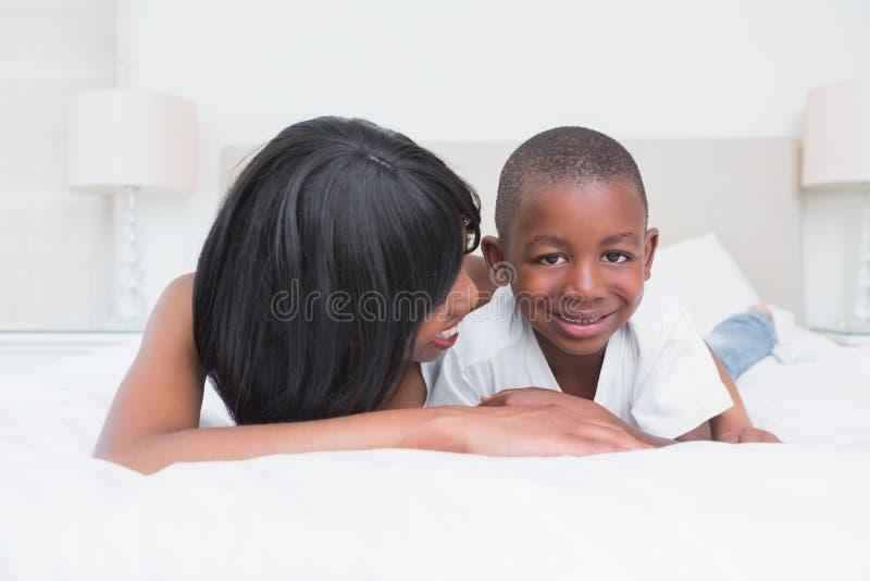 有他的儿子的俏丽的母亲在床上 免版税图库摄影