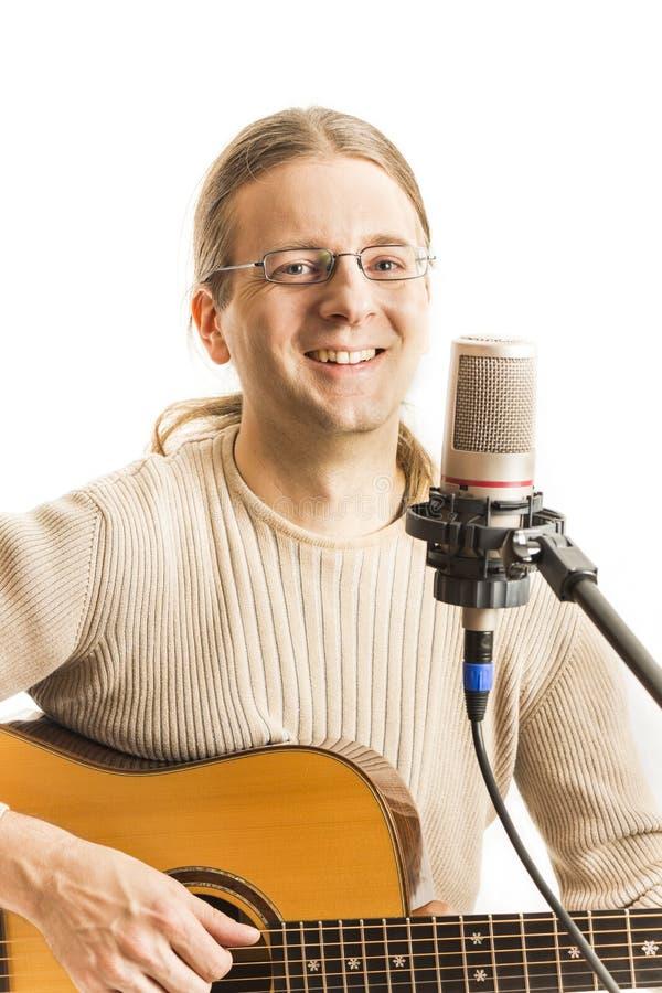 有他的吉他的微笑的音乐家 库存图片