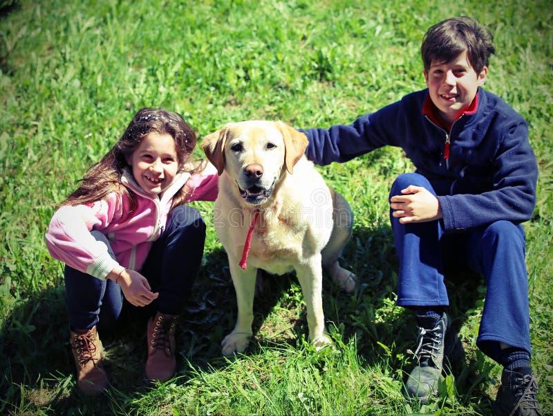 有他们的大拉布拉多狗的两个孩子 免版税库存照片