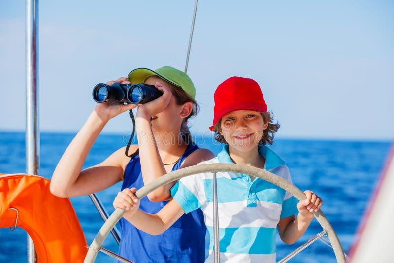 有他的姐妹的男孩上尉在船上在夏天巡航的航行游艇 旅行冒险,乘快艇与家庭的孩子 库存照片