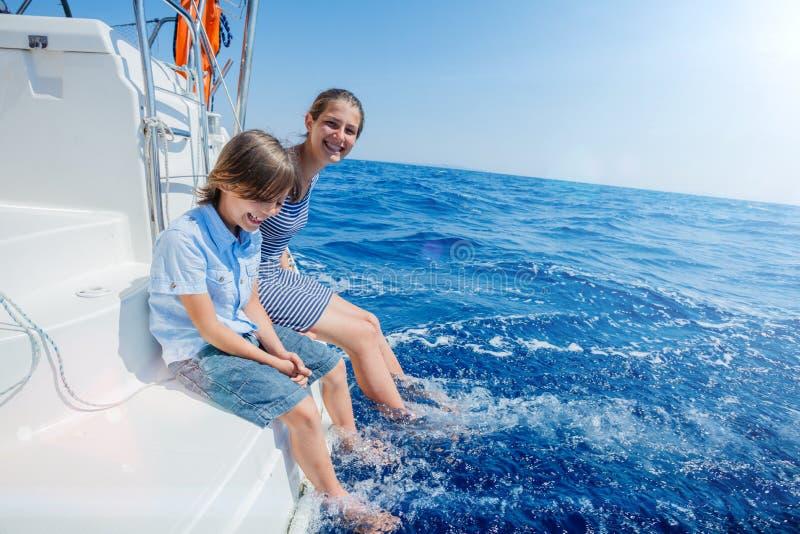 有他的姐妹的男孩在船上在夏天巡航的航行游艇 旅行冒险,乘快艇与孩子家庭度假 库存照片