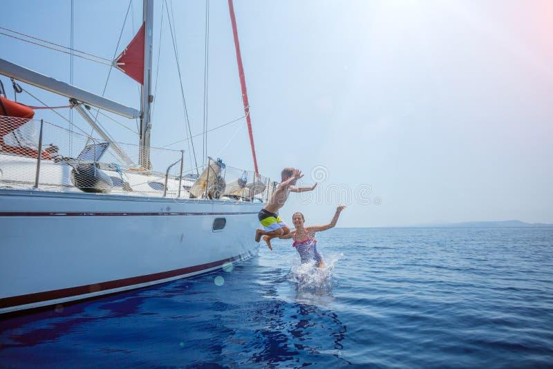 有他的姐妹的男孩跳在夏天巡航的航行游艇 旅行冒险,乘快艇与孩子 库存图片