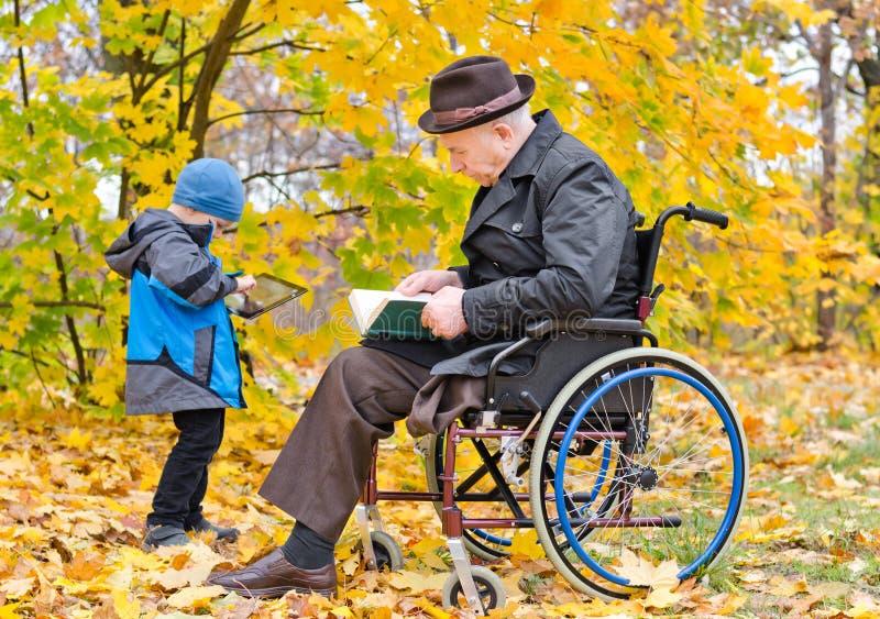 有他的孙子的年长残疾人 免版税库存照片