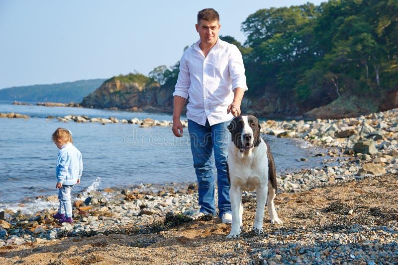 有他的小女儿和走在海滩的狗的爸爸 免版税库存图片