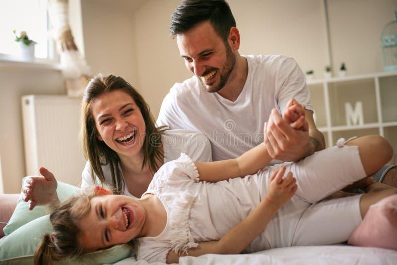 有他们的小女儿的父母在床上 图库摄影