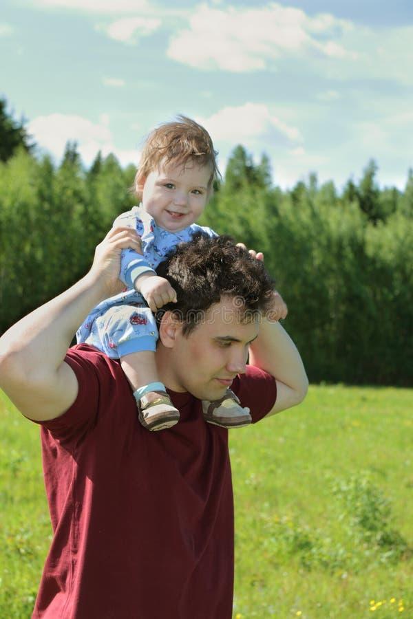 有他的小逗人喜爱的儿子的年轻人肩膀的 图库摄影