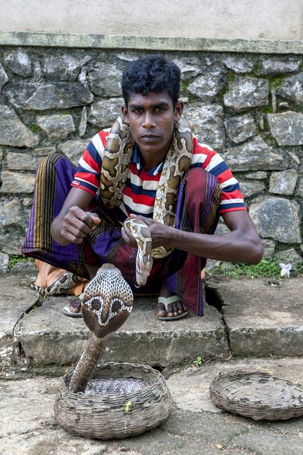有他的摆在为照片的眼镜蛇和Python的一位耍蛇者在Pinnawela在斯里兰卡 免版税库存照片