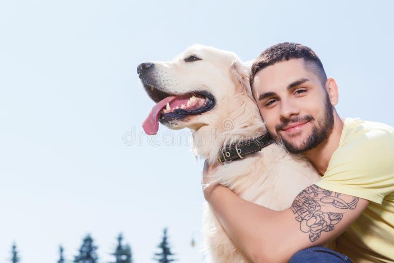 有他的狗的英俊的人 库存图片