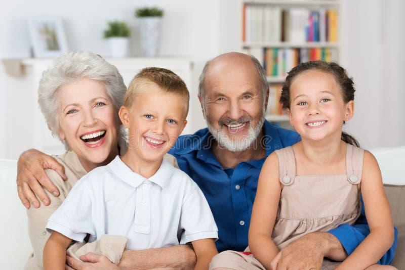 有他们的祖父母的愉快的年轻兄弟姐妹 免版税库存照片