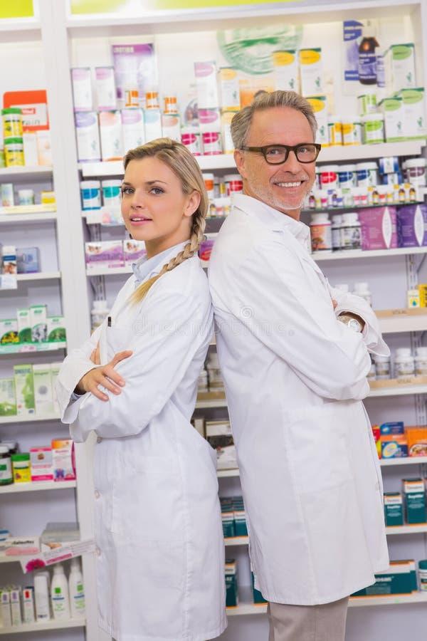 有他的站立与胳膊的实习生的药剂师横渡 免版税库存照片