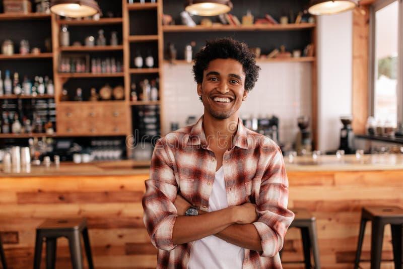 有他的胳膊的英俊的年轻人在咖啡馆横渡了 图库摄影