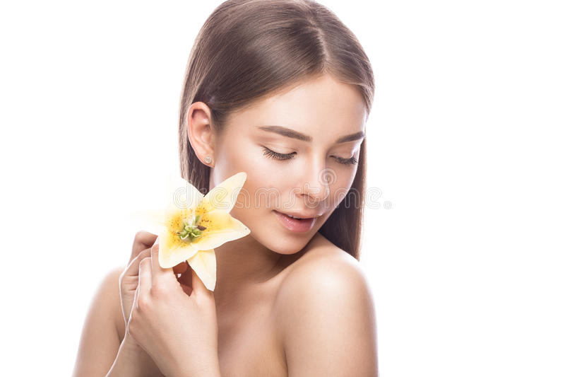 有轻的自然构成的美丽的女孩和与花的完善的皮肤在她的手上 秀丽表面 免版税库存图片