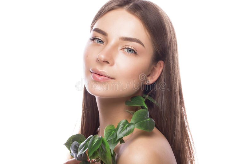 有轻的自然构成的美丽的女孩和与绿色分支的完善的皮肤在她的手上 秀丽表面 免版税图库摄影