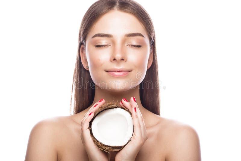 有轻的自然构成的美丽的女孩和完善的皮肤用椰子在她的手上 秀丽表面 库存图片