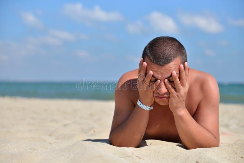 有头的英俊的年轻人在他的手上,说谎对sunbath 免版税库存照片