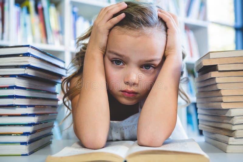 有头的被注重的女孩在手中在学校图书馆 免版税库存照片