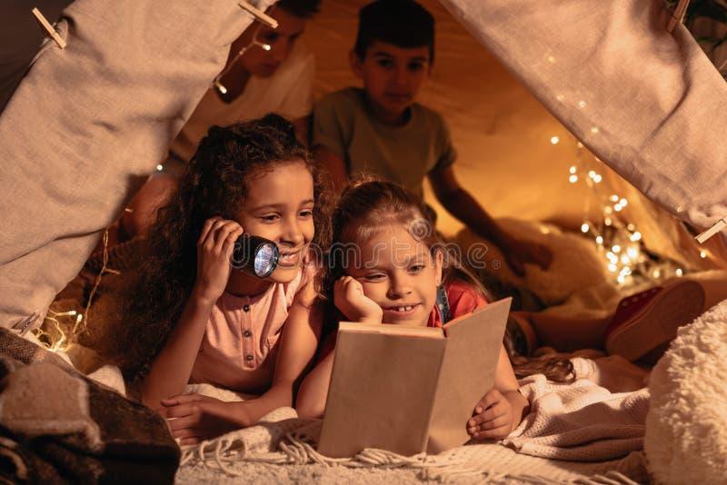 有更轻的阅读书的女孩在手工制造帐篷在家 免版税库存图片