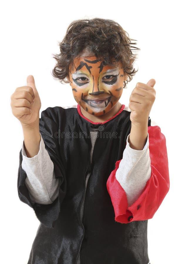 有他的面孔的愉快的年轻男孩被绘象老虎 免版税库存图片