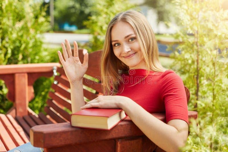 有轻的直发和雀斑的愉快的学生女性在红色毛线衣在握她的手的长凳坐大红色书挥动 免版税库存照片