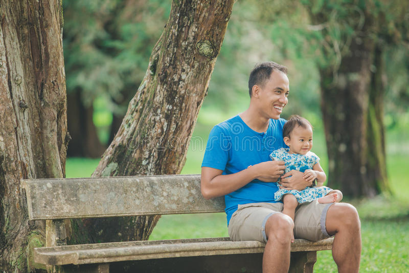 有他的婴孩的父亲在公园 免版税库存图片