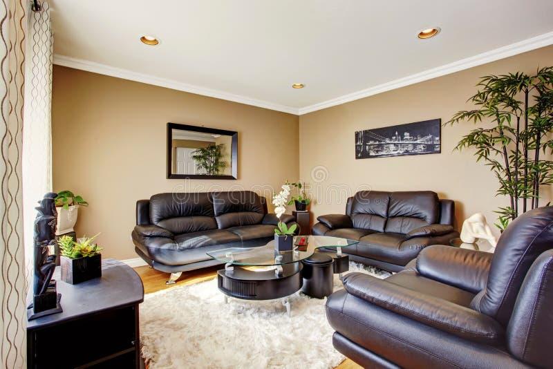 有黑皮革沙发集合和现代咖啡桌的舒适和豪华客厅 免版税图库摄影