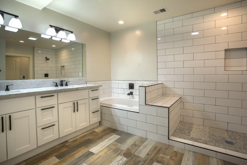有浴盆和瓦片阵雨的主要卫生间在有木地板的圣地亚哥 免版税库存照片