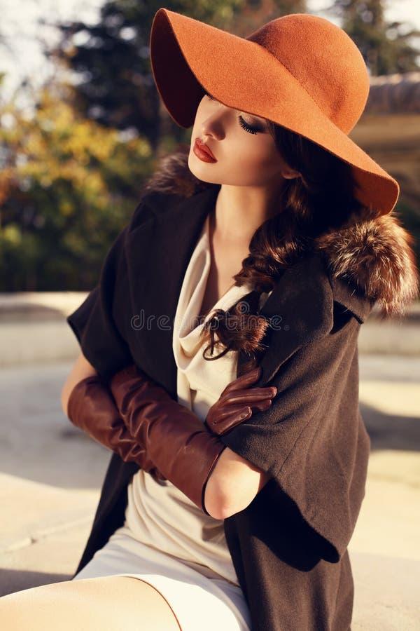 有戴着典雅的外套、帽子和手套的黑发的美丽的女孩 免版税库存照片