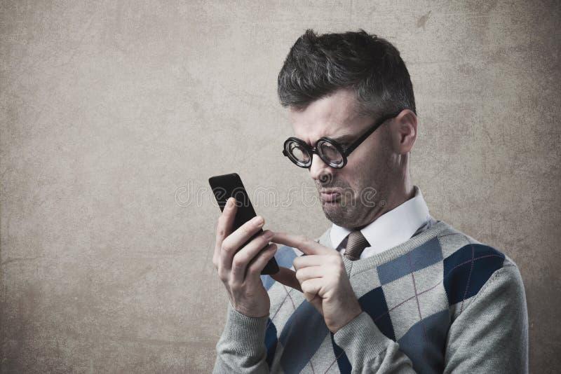 有滑稽的人与他的智能手机的困难 免版税库存照片