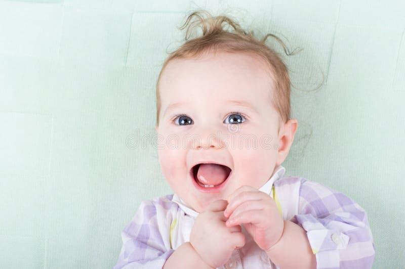 有滑稽的卷发的愉快地笑可爱的女婴 免版税库存照片