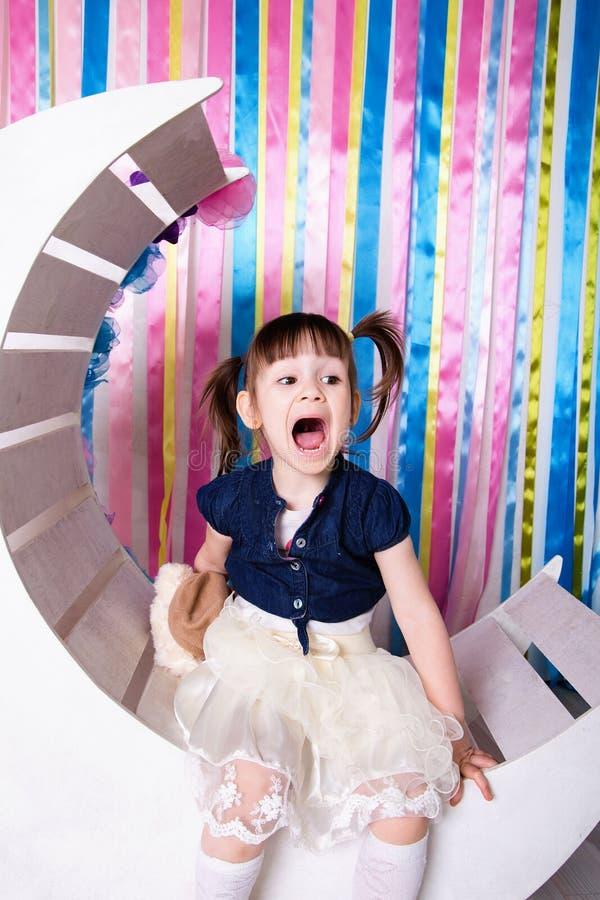 有滑稽的尾巴的一个快乐的小女孩 免版税库存照片