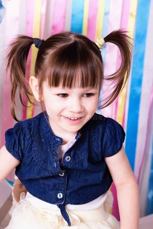 有滑稽的尾巴的一个快乐的小女孩 免版税图库摄影