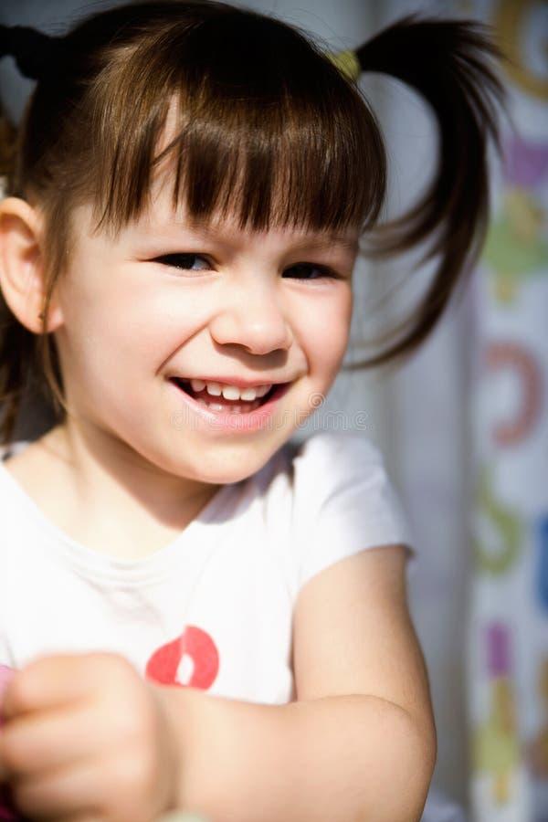 有滑稽的尾巴的一个快乐的小女孩 库存照片