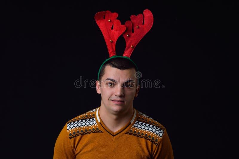年轻有滑稽的表示的人佩带的驯鹿垫铁 滑稽的i 免版税库存照片
