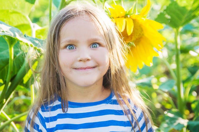 有滑稽的面孔的女孩在被归档的向日葵中 库存图片