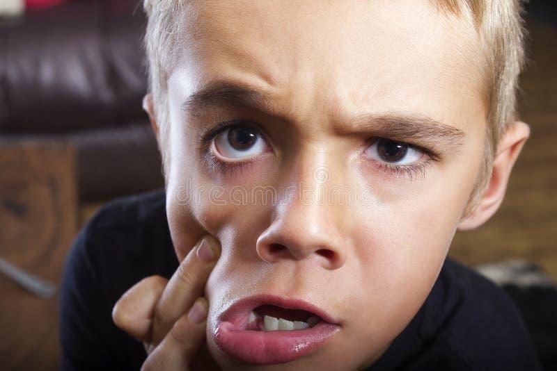 有滑稽的面孔的逗人喜爱和滑稽的年轻男孩 库存图片