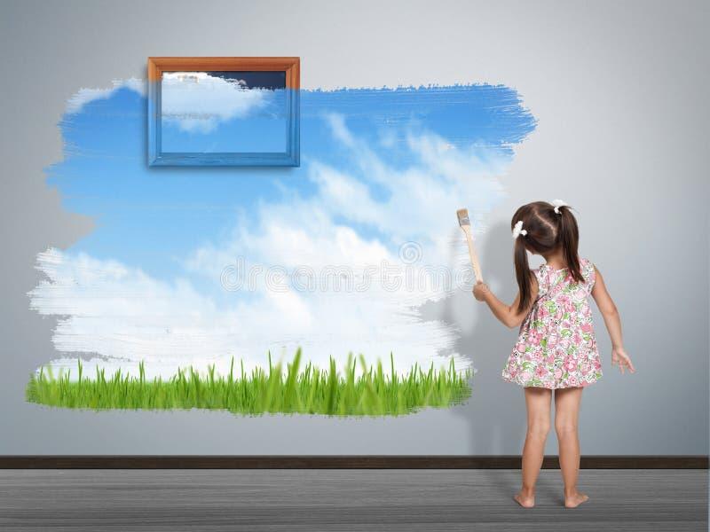 有画笔绘画墙壁的儿童女孩在自然的颜色 免版税图库摄影