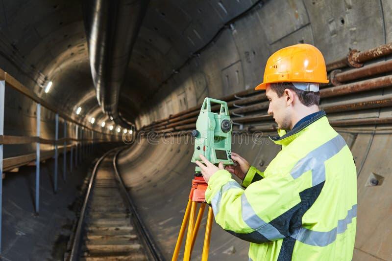 有经纬仪水平的测量员在地下铁路隧道建筑工作 免版税库存照片