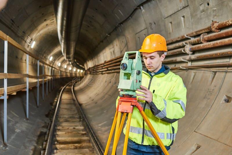 有经纬仪水平的测量员在地下铁路隧道建筑工作 库存图片